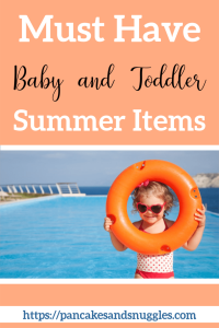toddler in bathing suit and sunglasses holding up orange swim donut by water