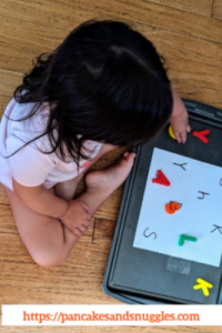 toddler playing with magnetic alphabets on cookie sheet
